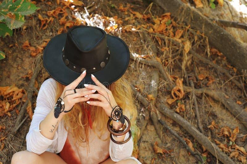Manos femeninas hermosas con las pulseras elegantes del dreamcatcher del boho y el sombrero de cuero negro fotos de archivo libres de regalías