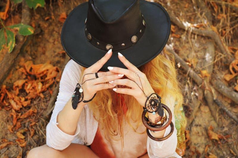 Manos femeninas hermosas con las pulseras elegantes del dreamcatcher del boho y el sombrero de cuero negro imagen de archivo
