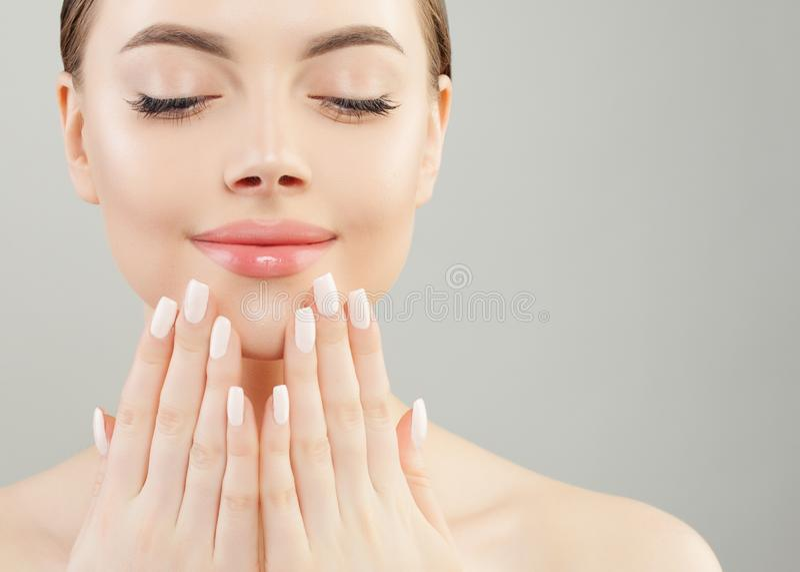 Manos femeninas hermosas con los clavos blancos contra maquillaje rosado de los labios Concepto de la manicura fotos de archivo