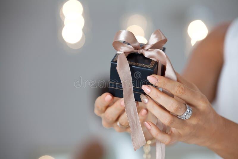 Manos femeninas hermosas que sostienen una pequeña caja de regalo fotografía de archivo libre de regalías