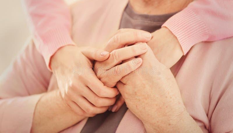 Manos femeninas jovenes que abrazan a la mujer mayor, foto de archivo libre de regalías