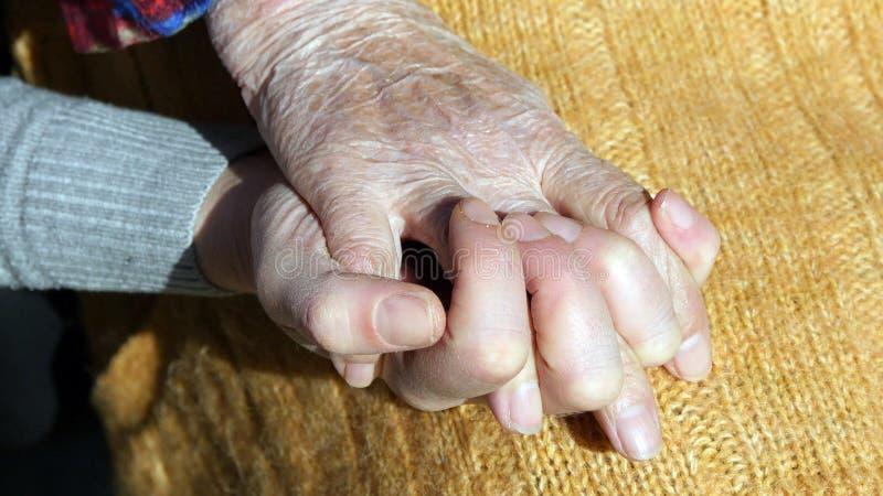 Manos femeninas jovenes que confortan un par mayor de manos del cierre al aire libre de la abuela para arriba fotos de archivo