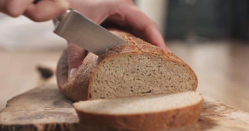 Manos femeninas jovenes que cortan el pan rústico del trigo del centeno en tabla de cortar fotos de archivo libres de regalías