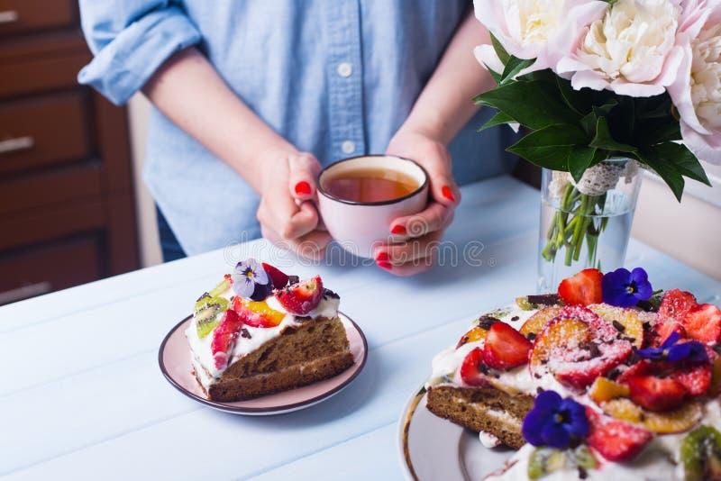Manos femeninas jovenes que sostienen la taza de té cerca de la placa con la torta de la crema agria con las frutas adornadas con imágenes de archivo libres de regalías