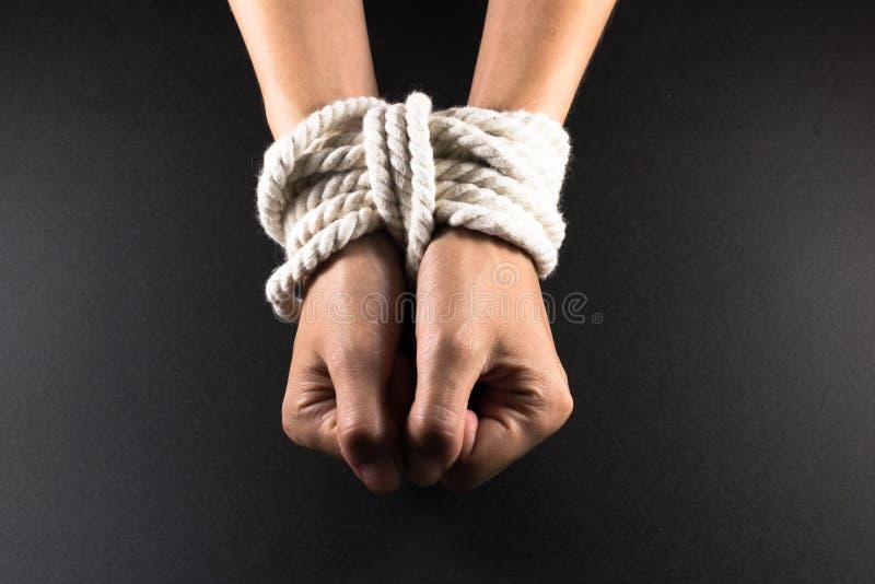 Manos femeninas limitadas en esclavitud con la cuerda fotografía de archivo