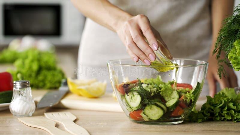 Manos femeninas que añaden el aceite de oliva a la ensalada de las verduras frescas, forma de vida vegetariana imágenes de archivo libres de regalías