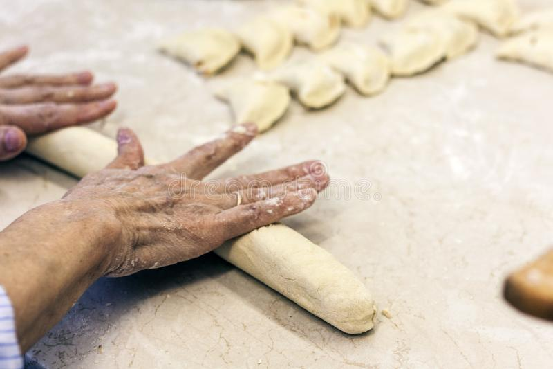 Manos femeninas que amasan haciendo la pasta para las bolas de masa hervida imagenes de archivo