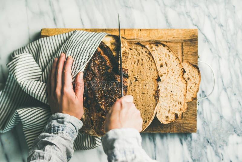 Manos femeninas que cortan el pan de pan amargo recientemente cocido imagenes de archivo