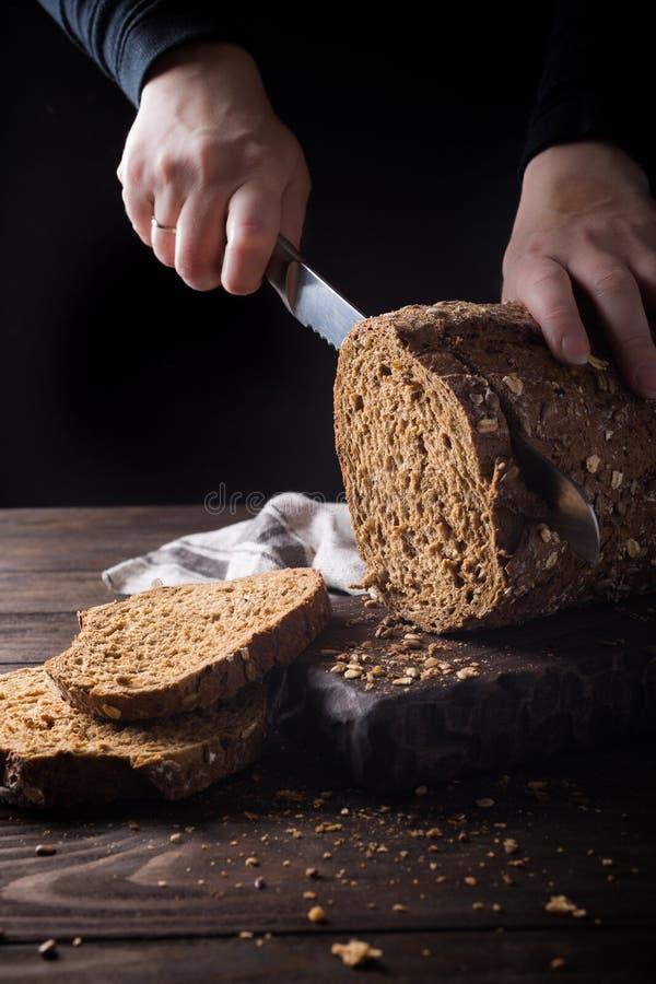 Manos femeninas que cortan el pan hecho en casa del multigrain imagenes de archivo