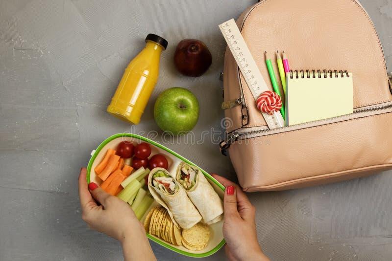 Manos femeninas que embalan la cena en caja del almuerzo en la tabla gris imagen de archivo libre de regalías