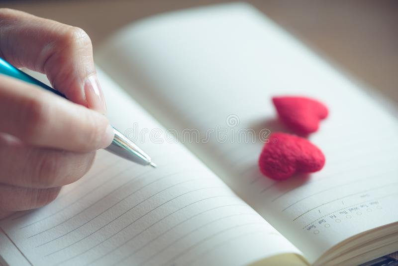 Manos femeninas que escriben en cuaderno abierto con el pequeño corazón rojo de los pares fotografía de archivo libre de regalías