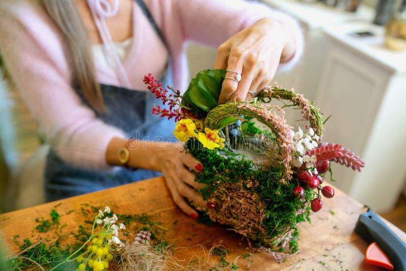 Manos femeninas que hacen el ramo hermoso de flores en fondo imagenes de archivo
