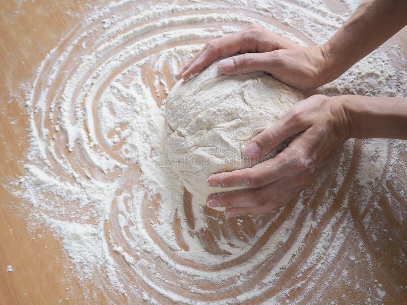 Manos femeninas que hacen la pasta para la pizza Pasta cruda rodante imagen de archivo
