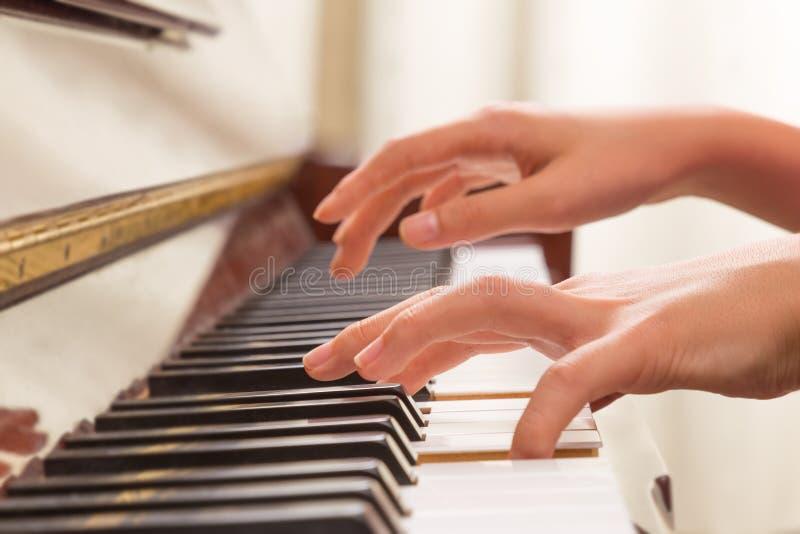 Manos femeninas que juegan el piano fotografía de archivo