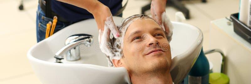 Manos femeninas que lavan el pelo al hombre sonriente hermoso fotografía de archivo