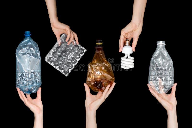 Manos femeninas que llevan a cabo la basura machacada vacía del plástico, lámpara aislada en fondo negro Basura reciclable Recicl fotos de archivo