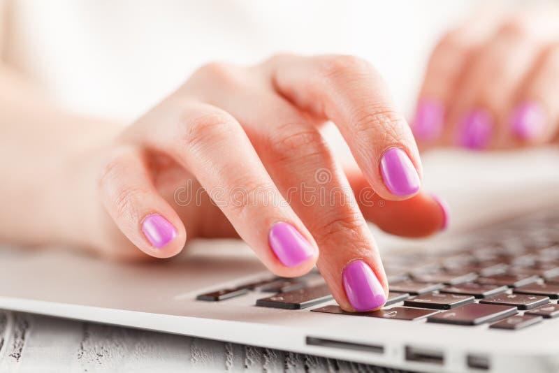 Manos femeninas que mecanografían en el ordenador portátil, en fondo brillante fotografía de archivo libre de regalías