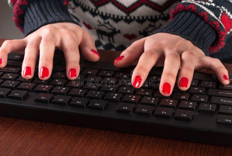 Manos femeninas que mecanografían en el teclado de ordenador en la tabla imágenes de archivo libres de regalías