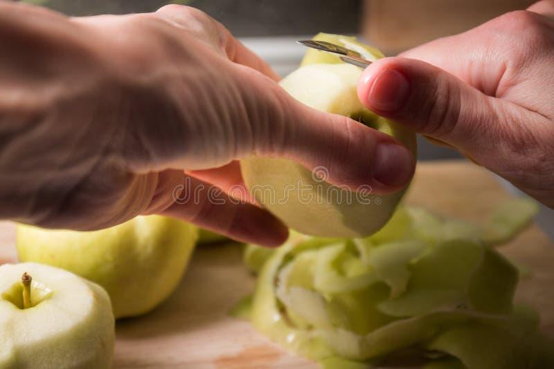 Manos femeninas que pelan la piel apagado de la manzana verde usando un cuchillo de pelado imagenes de archivo