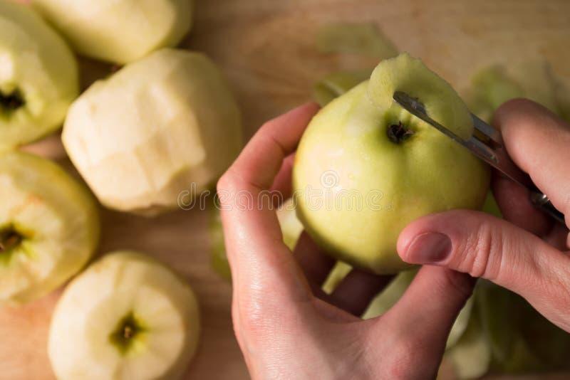 Manos femeninas que pelan la piel apagado de la manzana verde usando un cuchillo de pelado imágenes de archivo libres de regalías