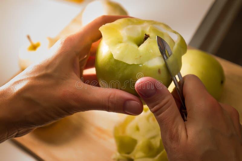 Manos femeninas que pelan la piel apagado de la manzana verde usando un cuchillo de pelado imagen de archivo libre de regalías