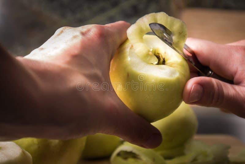Manos femeninas que pelan la piel apagado de la manzana verde usando un cuchillo de pelado foto de archivo
