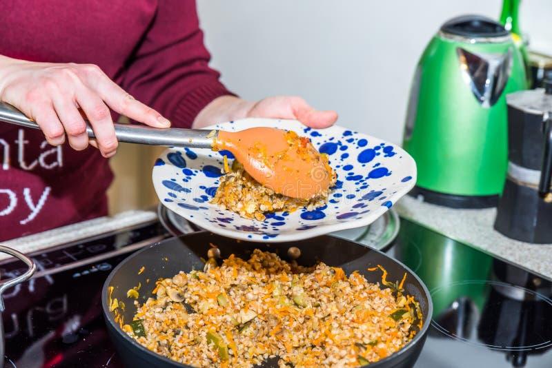 Manos femeninas que ponen porciones cocinadas del buckweat a las placas coloridas sobre la cocina eléctrica moderna en cocina fotos de archivo