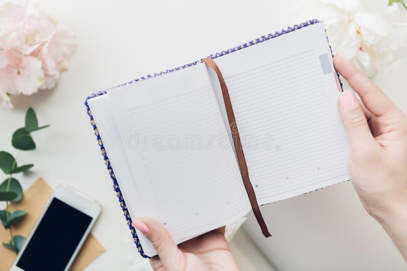 Manos femeninas que sostienen el cuaderno vacío en el fondo de flores y del teléfono Visión superior Mofa para arriba imágenes de archivo libres de regalías