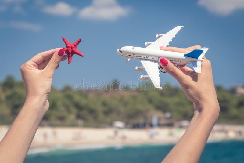 Manos femeninas que sostienen el juguete del aeroplano y la estrella de mar contra el beaut fotos de archivo