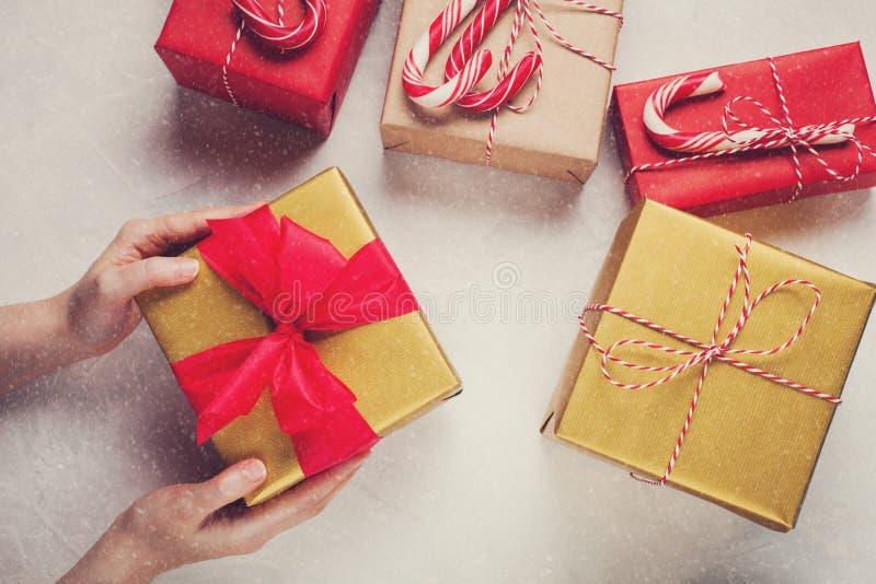 Manos femeninas que sostienen el regalo de la Navidad con la decoración hecha a mano en un fondo concreto blanco fotos de archivo libres de regalías