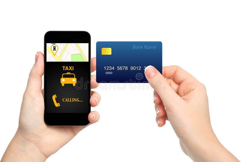 Manos femeninas que sostienen el teléfono con el taxi y la tarjeta de crédito o del interfaz foto de archivo