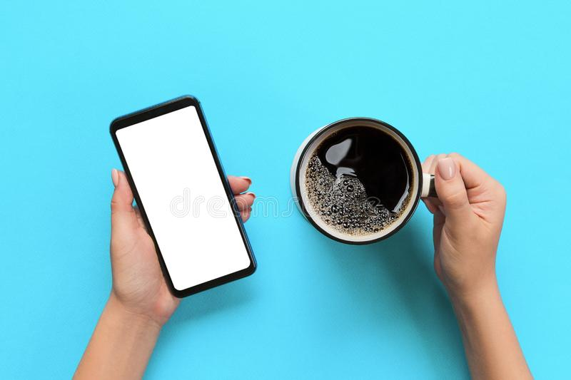 Manos femeninas que sostienen el teléfono móvil negro con la pantalla y la taza blancas en blanco de café Imagen de la maqueta co fotos de archivo libres de regalías