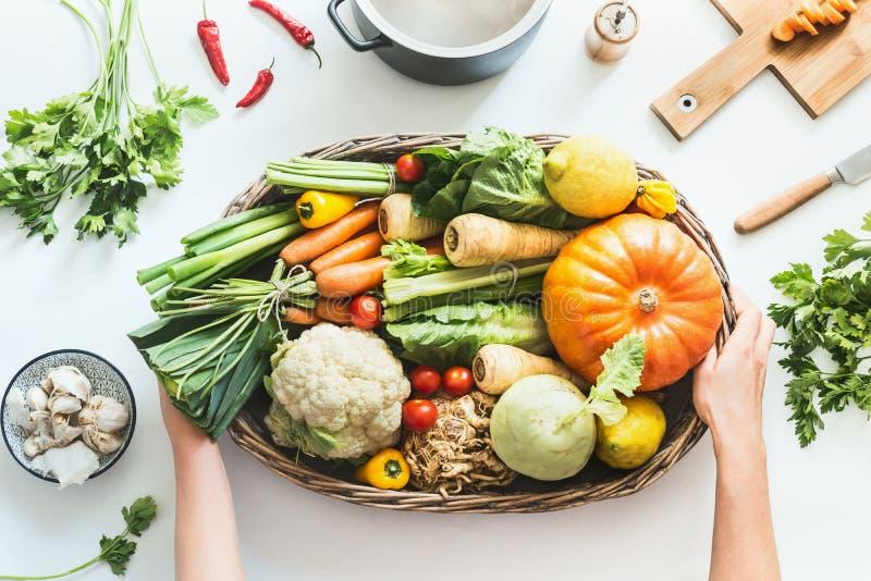 Manos femeninas que sostienen la bandeja con las diversas verduras orgánicas coloridas de la granja en el fondo blanco del escrit fotos de archivo