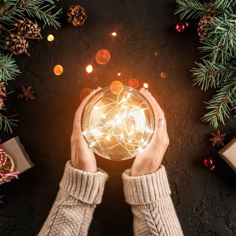 Manos femeninas que sostienen la bola que brilla intensamente de la Navidad en fondo del día de fiesta con las ramas del abeto, r foto de archivo