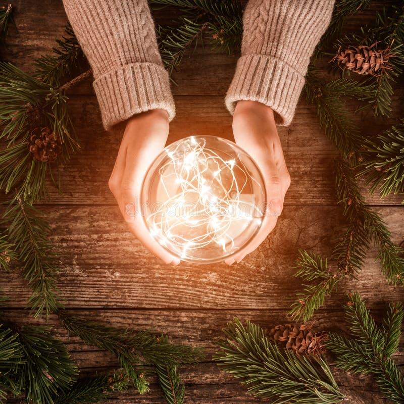 Manos femeninas que sostienen la bola que brilla intensamente de la Navidad en fondo del día de fiesta con las ramas del abeto Ta imagenes de archivo