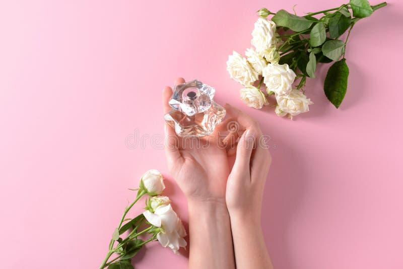 Manos femeninas que sostienen la botella de perfume y de flores en fondo del color foto de archivo libre de regalías