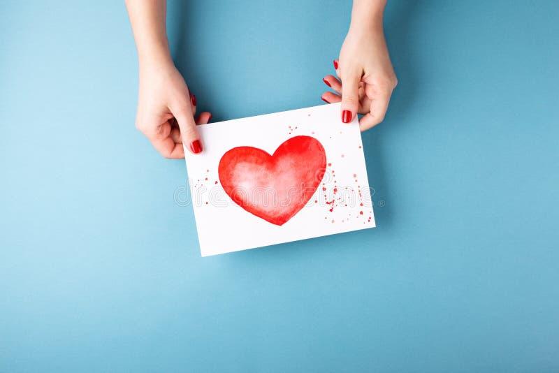 Manos femeninas que sostienen la tarjeta con el corazón en fondo azul foto de archivo
