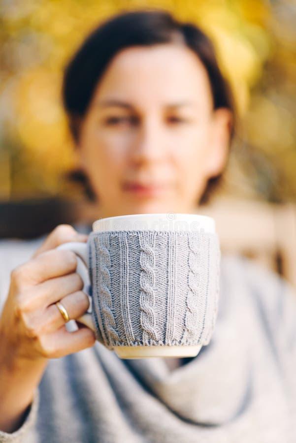 manos femeninas que sostienen la taza de café caliente del té en paisaje del otoño - imágenes de archivo libres de regalías