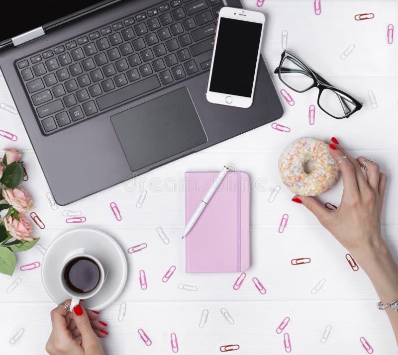Manos femeninas que sostienen la taza de caf? y de bu?uelo mientras que trabaja en espacio de trabajo de la oficina foto de archivo libre de regalías