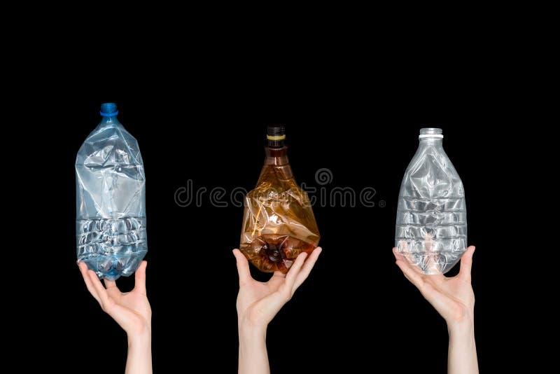 Manos femeninas que sostienen las botellas plásticas machacadas vacías aisladas en fondo negro Basura reciclable Reciclando, reut imagenes de archivo
