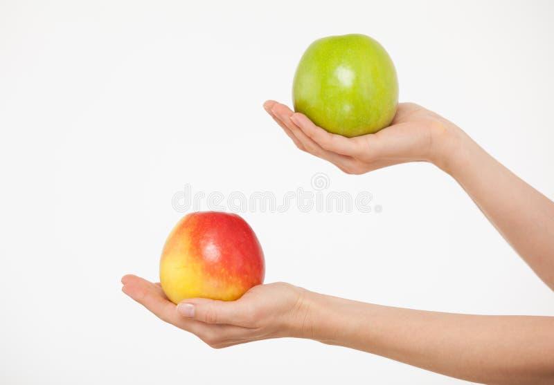 Manos femeninas que sostienen manzanas rojas y verdes foto de archivo libre de regalías