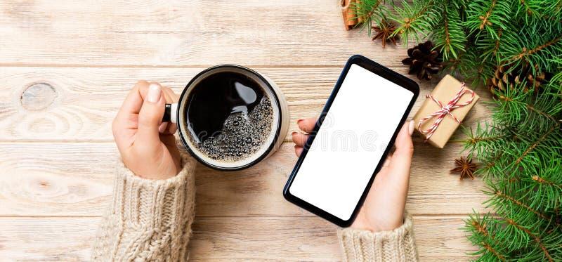 Manos femeninas que sostienen smartphone moderno con el mosk para arriba y la taza de caf? en la tabla de madera con la decoraci? imagen de archivo