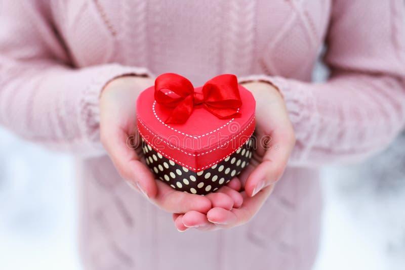 Manos femeninas que sostienen un regalo encajonado de corazón El día de tarjetas del día de San Valentín y la tarjeta de Navidad imagen de archivo libre de regalías