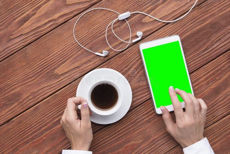 Manos femeninas usando la tableta de la maqueta y la taza digitales de café y de auriculares blancos en el escritorio de madera m imagen de archivo libre de regalías