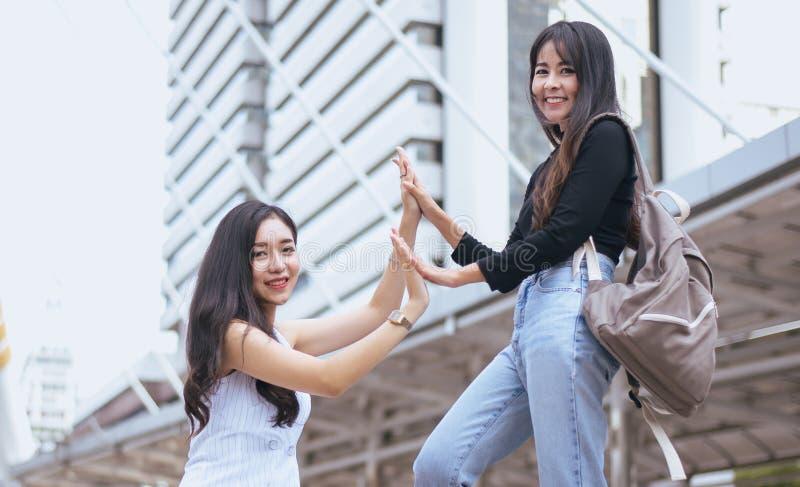 Manos hermosas asiáticas que se encuentran, saludo feliz de la mujer de dos amigos de los pares en el centro urbanos foto de archivo libre de regalías