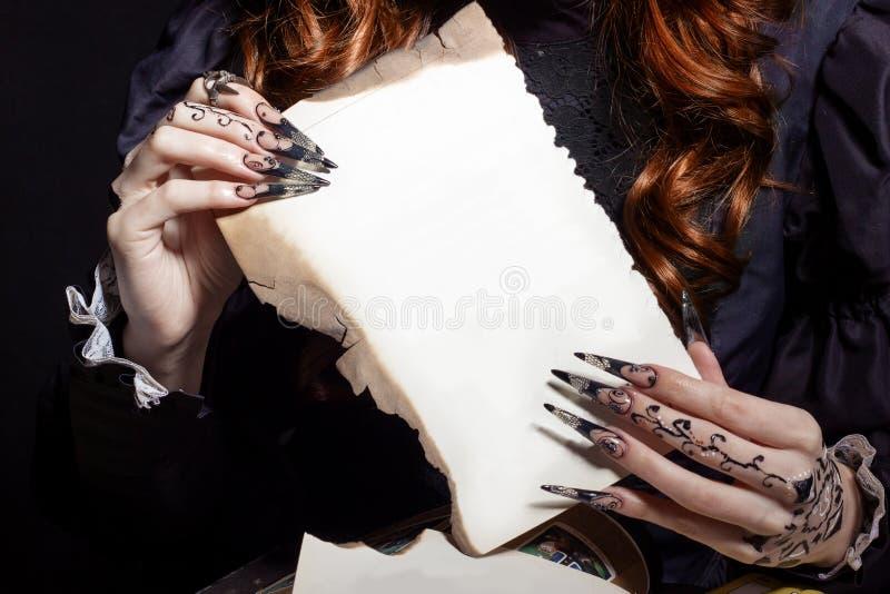 Manos hermosas con los clavos negros largos que sostienen la hoja blanca fotos de archivo
