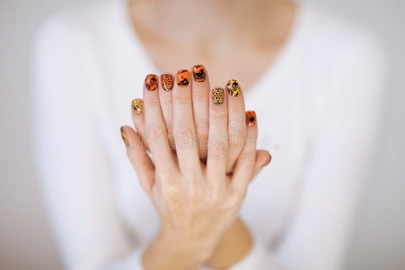 Manos hermosas de la mujer con el esmalte de uñas lindo de Halloween fotos de archivo libres de regalías
