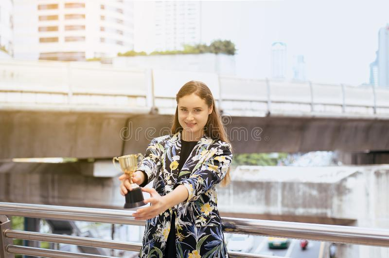 Manos hermosas de la mujer de negocios que sostienen la taza de oro del trofeo concepto al aire libre, del éxito y de la victoria fotografía de archivo libre de regalías