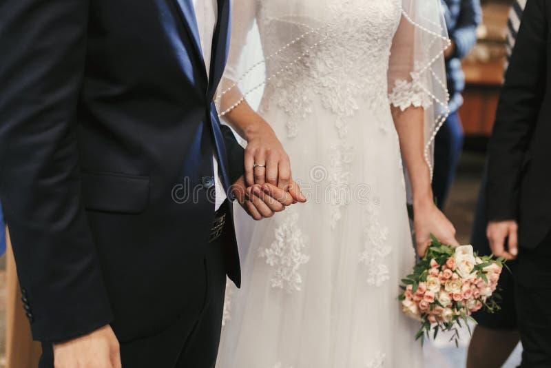 Manos hermosas de novia y del novio que intercambian los anillos de bodas en chur foto de archivo