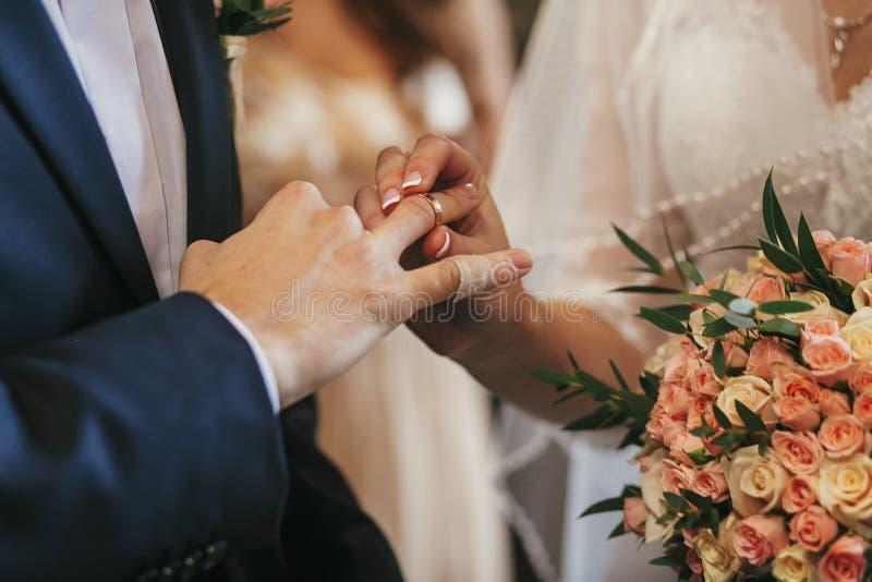 Manos hermosas de novia y del novio que intercambian los anillos de bodas en chur imágenes de archivo libres de regalías